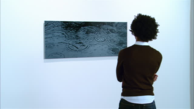 Rear view of young man looking at artwork at exhibition of contemporary art
