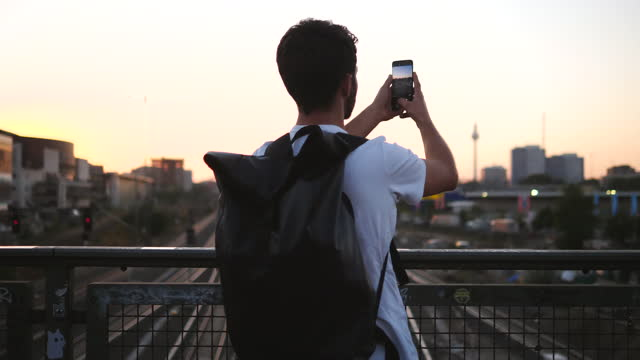 rear view of young man standing on footbridge photographing city during sunset - photographing stock videos & royalty-free footage