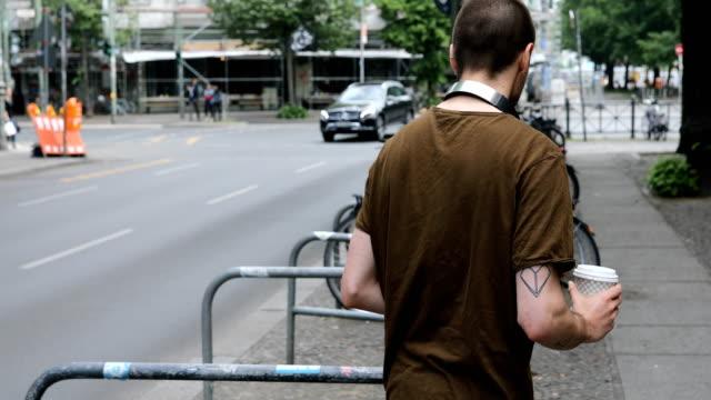 vidéos et rushes de vue arrière du jeune homme qui marche sur le trottoir en ville - mode of transport