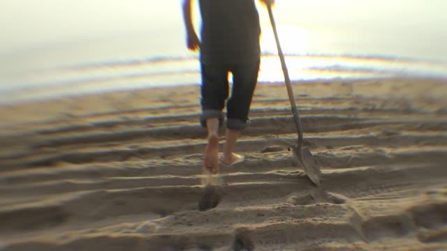 pov rear view of young man walking toward ocean with shovel / los angeles, california, usa - nur junge männer stock-videos und b-roll-filmmaterial