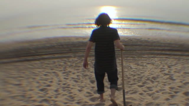 ms ws rear view of young man walking toward ocean with shovel / los angeles, california, usa - medium length hair stock videos & royalty-free footage