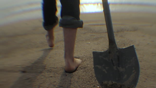 pov rear view of young man walking toward ocean with shovel, low section / los angeles, california, usa - nur junge männer stock-videos und b-roll-filmmaterial
