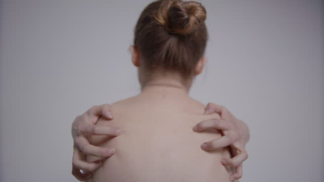 Rear view of young, naked woman grasping her own back