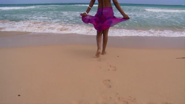 SLO MO, WS, Rear view of young woman facing ocean, Punta Cana, Dominican Republic