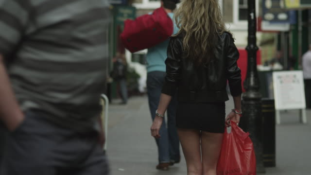 ms tu ws rear view of young woman in mini skirt walking on sidewalk / london, uk - long stock videos and b-roll footage