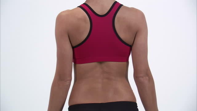 cu rear view of young woman in sports bra with hands on hips, mid section / orem, utah, usa - sports bra stock videos & royalty-free footage