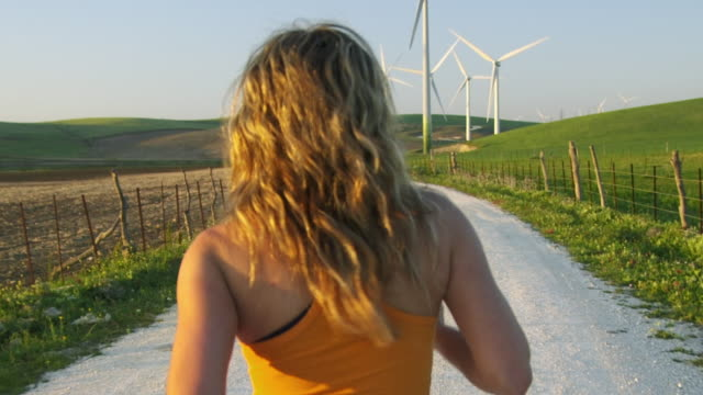 stockvideo's en b-roll-footage met ms rear view of young woman jogging on gravel road through wind farm set in green fields near tarifa / cadiz, spain - volgen activiteit