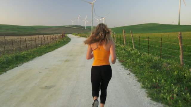 ws rear view of young woman jogging on gravel road through wind farm set in green fields near tarifa / cadiz, spain - following stock videos & royalty-free footage