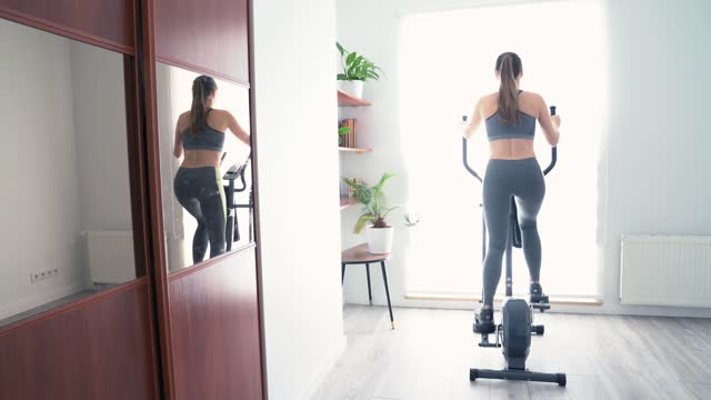 rear view of young woman on cross trainer at home - cross trainer stock videos & royalty-free footage