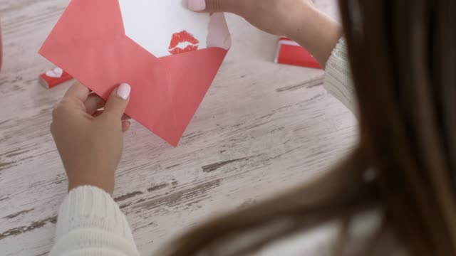 rear view of young woman opening her love letter - valentine's day stock videos & royalty-free footage