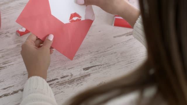 彼女のラブレターを開く若い女性の背面図 - バレンタインデー点の映像素材/bロール