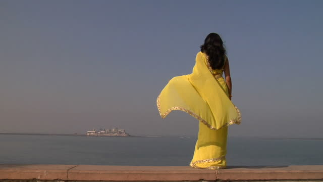 WS, Rear view of young woman standing on wall, facing Haji Ali Dargah, Mumbai, Maharashtra, India