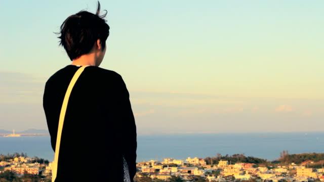 背面ビューに立っている若い女性。 - 見つめる点の映像素材/bロール