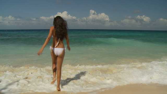 ws rear view of young woman walking into sea / seychelles - 人の腕点の映像素材/bロール