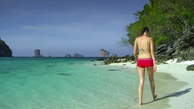 WS Rear view of young woman walking on tropical beach, Krabi, Thailand