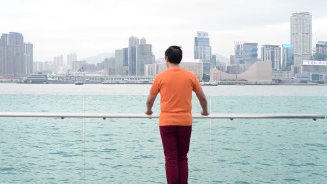 vidéos et rushes de vue arrière sur l'homme à la recherche de victoria harbour hong kong - regarder ailleurs