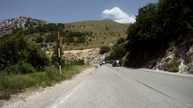 stockvideo's en b-roll-footage met rear view onboard on mountain road: motorcycle riders - racewagen