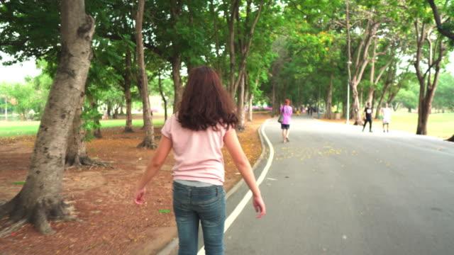 vidéos et rushes de vue arrière : une fille heureuse d'adolescent jouant le patin à roulettes dans le stationnement public le matin du week-end - suivre activité avec mouvement