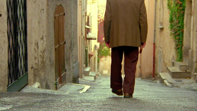 Rear view pan zoom in senior man with cane walking down steep village road / Biot, France