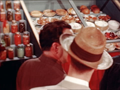 stockvideo's en b-roll-footage met 1946 rear view people looking at display of pastries and desserts at state fair / industrial /audio - 1946