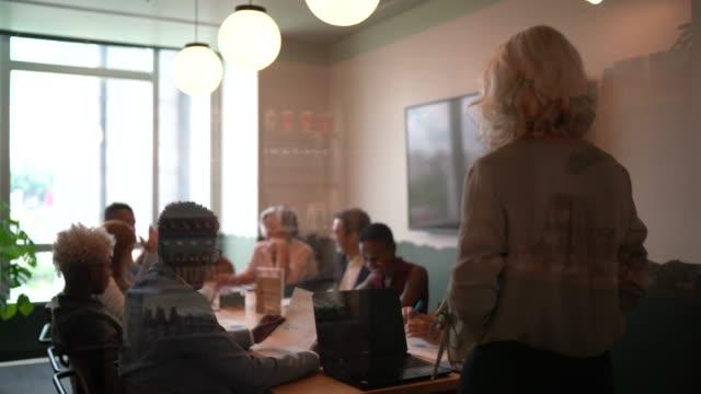 rückansicht - reflexion von geschäftsleuten in einem vorstandssitzungsraum - vortrag stock-videos und b-roll-filmmaterial