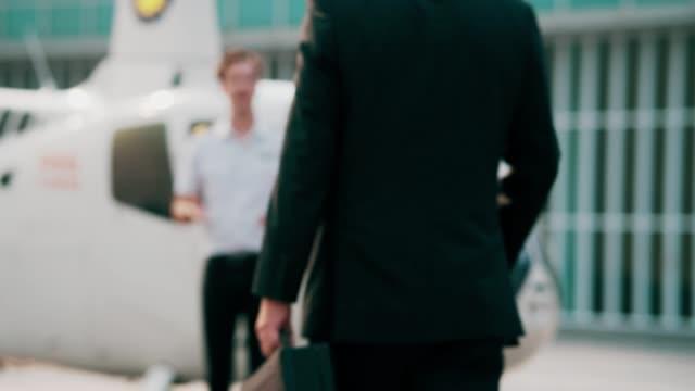 vidéos et rushes de vue arrière : homme d'affaires aîné marchant vers l'hélicoptère - première classe