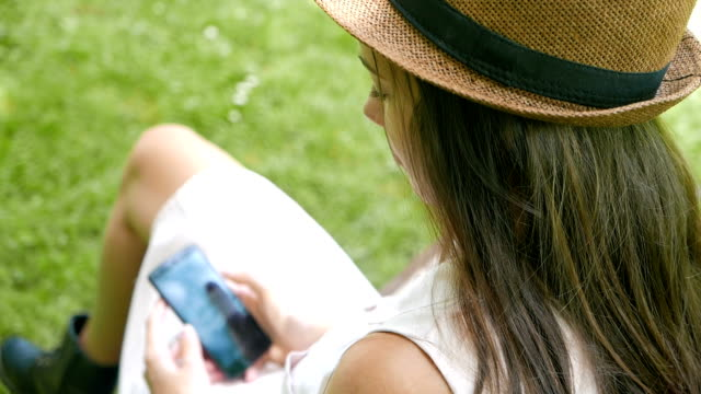 Rear view shot of a young adult girl sitting on a becnh outdoors and using her smart phone