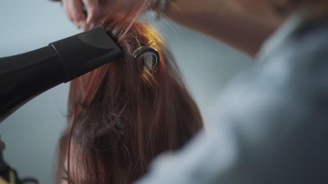 vista posteriore slow motion asiatica cinese parrucchiere femminile che soffia pettinando i capelli lunghi bagnati per il suo cliente nel salone dei capelli - super slow motion video stock e b–roll