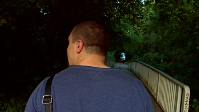 Rear view slow motion shot of a man taking a walk in the park and crossing a bridge