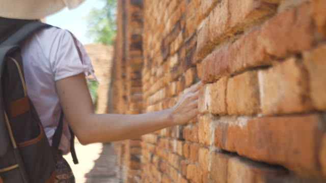 rear view slow motion woman slide hand against old red brick wall in slow motion. female hand touch rough surface of stone. travel in south east asia ayuttaya thailand, - toughness stock videos & royalty-free footage