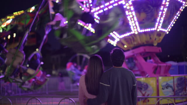 vidéos et rushes de ws rear view, teenage couple at a carnival at night - couple d'adolescents