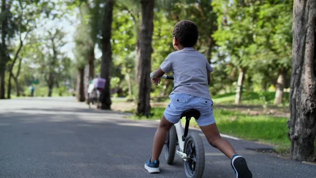 vídeos de stock, filmes e b-roll de retrovisor slo mo criança andando bicicleta de equilíbrio - usa