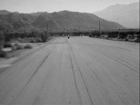rear view traveling shot along scenic desert road motorcycle speeding from around corner past camera / rear view traveling shot motorcycle cop riding... - two lane highway stock videos and b-roll footage