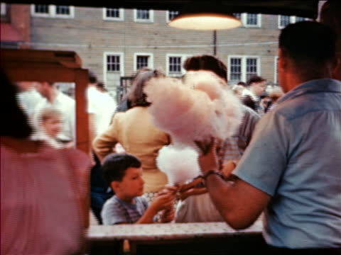 1946 rear view vendor giving cotton candy to people at State Fair / industrial /AUDIO