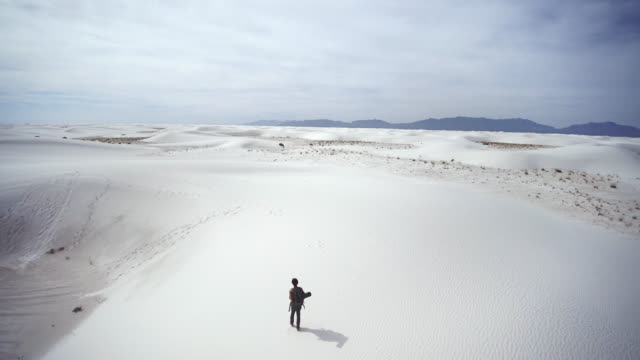 rear view video of the young caucasian man, tourist with the big backpack, walking through the sandy desert. white sands national monument, new mexico, usa.  aerial drone footage. - named wilderness area stock videos & royalty-free footage