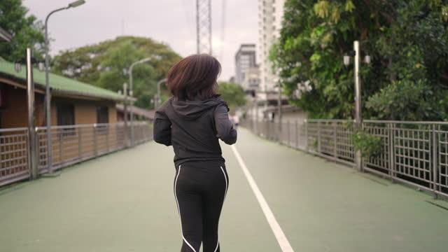 stockvideo's en b-roll-footage met de vrouw die van de achtermening op een stedelijke weg loopt - onherkenbaar persoon