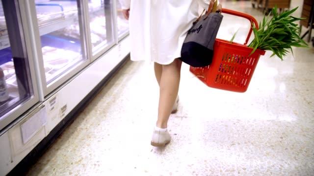 rückansicht: frau einkauf im supermarkt - low angle view stock-videos und b-roll-filmmaterial