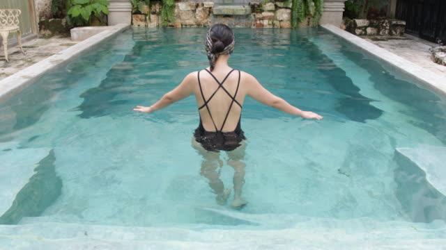 rear view woman walking into pool waist deep. - waist stock videos & royalty-free footage