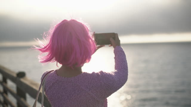 ms cu rear view woman with pink hair taking a photograph - pink hair stock videos & royalty-free footage
