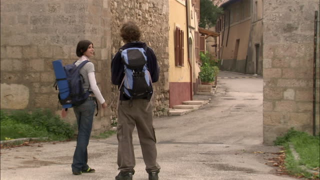 Rear view young backpacking couple walking  into village