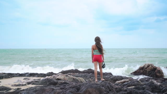 ws rear view young girl looking at the sea - 少女一人点の映像素材/bロール
