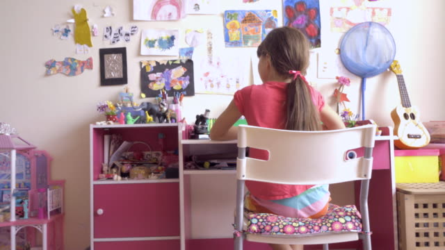 ms rear view young girl sits playing at her desk in her bedroom - one girl only stock videos & royalty-free footage