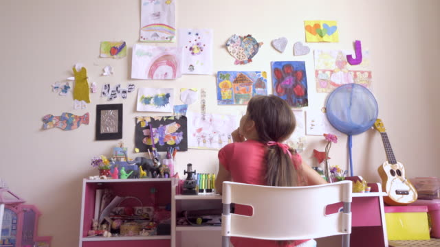 vidéos et rushes de ms rear view young girl sits playing at her desk in her bedroom - domestic room