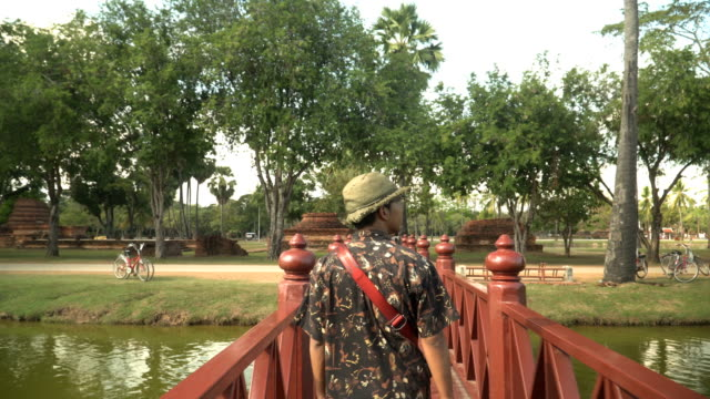 rear view: Young traveler is walking on bridge in ancient temple, Sukhothai under sunlight