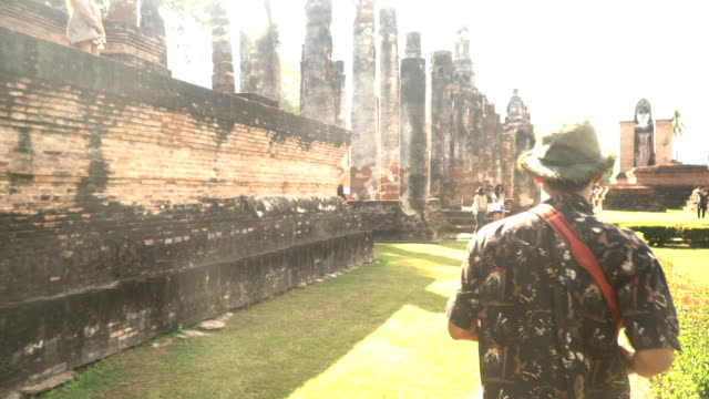 rear view: Young traveler is walking to in ancient temple, Sukhothai under sunlight
