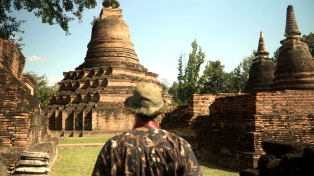 rear view: Young traveler is walking to in ancient temple, Sukhothai, Thailand