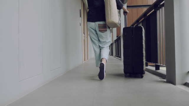 rear view : young woman carries suitcase - bagaglio video stock e b–roll