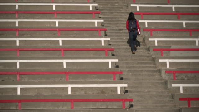 ws rear view young woman walking up stairs wearing a backpack - tribüne stock-videos und b-roll-filmmaterial