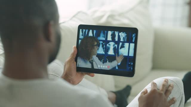 vídeos de stock, filmes e b-roll de visão traseira, close-up do homem negro africano usando chamada de vídeo tablet para o médico do sexo masculino sobre cuidados de saúde e medicamentos para explicar os pulmões de raio-x na clínica médica juntos. quarentena, dispositivo de informaç� - portable information device