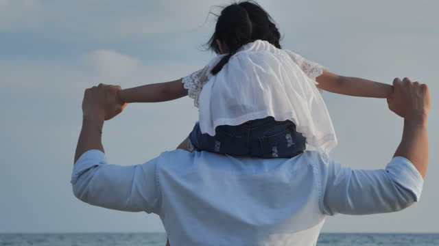 rear view,family of asian father and baby girl age 4 yearold ride the neck of father holding hand to her and looking at view outdoor on the beach together.happy family holidays.relations and people.open arms concept. - wonderlust stock videos & royalty-free footage